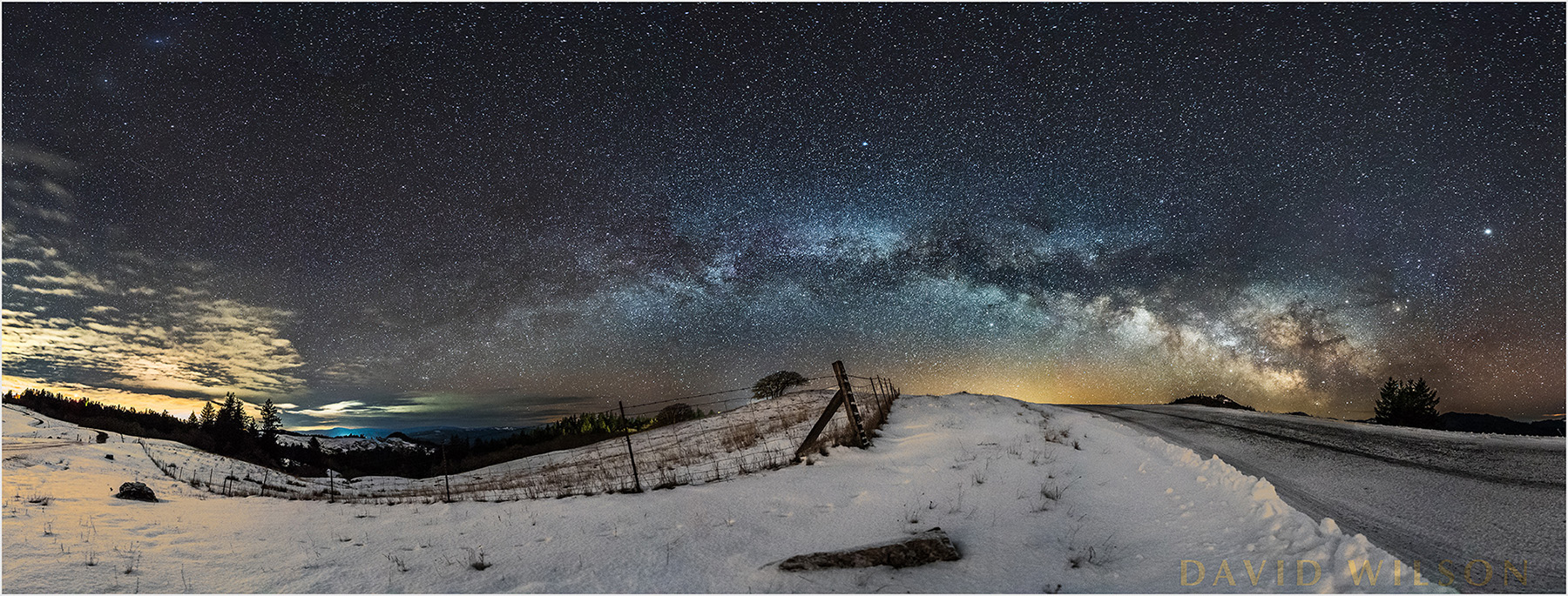 "This snowy pre-dawn scene is just outside of Kneeland, Humboldt County, CA. at 05:00 on February 21, 2018.At 03:30 I looked at my clock and felt so tired. But a voice said to me from inside, ""If you don't go out, you won't bring anything back.""""But sometimes a body needs sleep!""""Well, if you don't go out, you won't bring anything back.""""You always say that,"" I said. But I got up.I'd been to that spot and taken a few photos while photographing the Geminid Meteors with my son last December 13, 2017. The single silhouette is me, and then the double is both of us. Since I'd been here back in December, I knew the spot, the rise in the land as the road rounds that curve, and which way it was facing.I use an app called Sky Guide to tell me where in the sky celestial things will be, and when. I can look to see what will be visible tonight, next year, or last year, at any time of the day. Using that app, I knew that the Galactic Core of the Milky Way — the part with the greatest detail, contrast and color — would be rising low over the eastern horizon this time of year starting after 03:00. (Where it is at what time is different throughout the year).Thank goodness I'd been there in December, because from that I knew it was going to be the perfect spot to see the Milky Way before dawn began brightening the east. From what the app said, it looked like the Milky Way was going to be rising at a low angle above the horizon close above the horizon in the wee hours, and my memory of the spot put it right above the road where it makes that turn. My weather site said the sky cover would be less than 40% that morning, and that there'd be a little snow that night to add to what remained from the previous days. When I got there it was perfect, one of those beautiful gifts that keep coming my way. You can see that night's snowfall as a thin layer on the road."