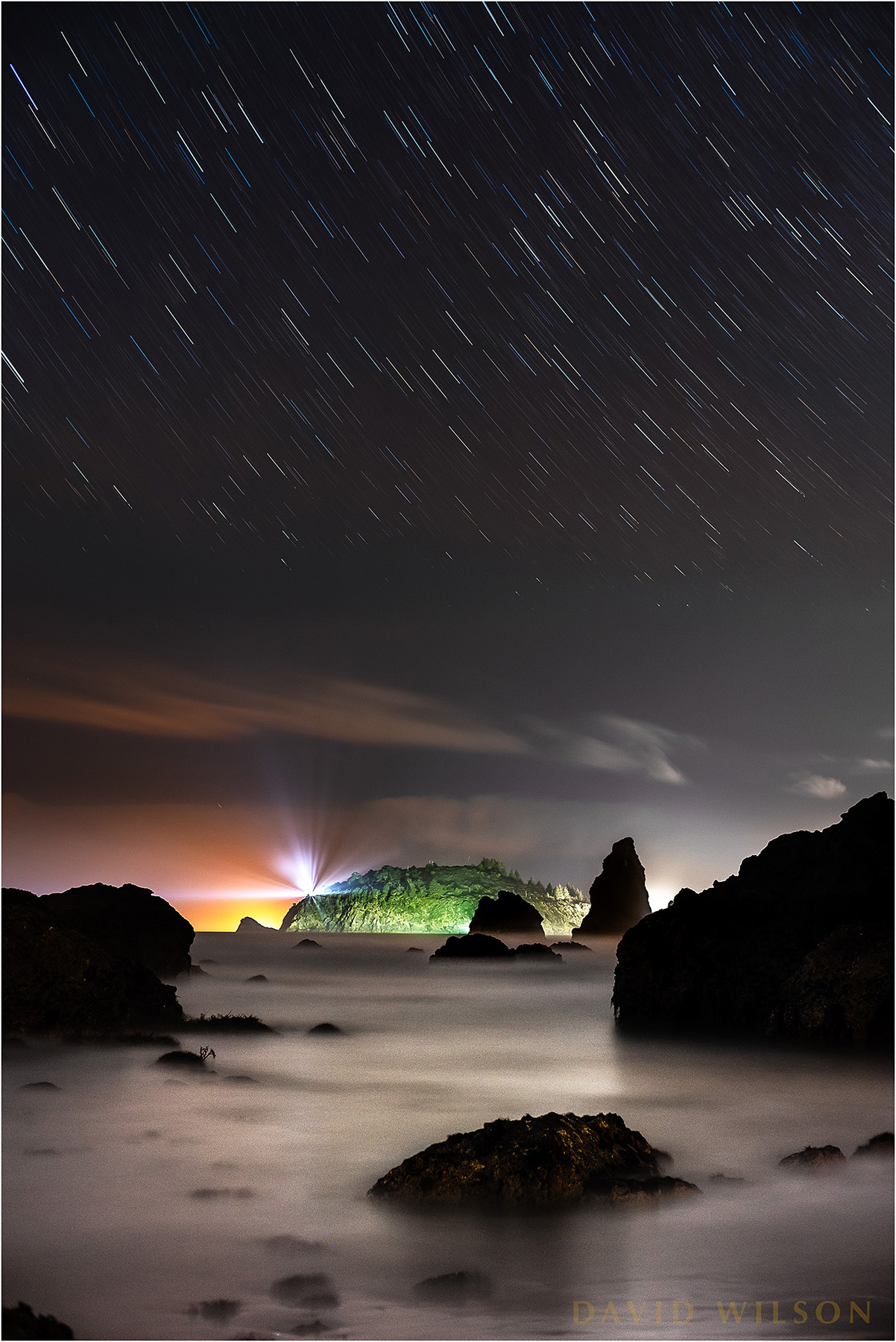 Looking north toward Trinidad and Trinidad Head from Houda Point Beach, Humboldt County, California. This is actually a little west of north, as you can see from the arc of the star trails that the North Star, Polaris, would be above and to the right of this view. The star trails closer to the cloud layer appear to break up in places due to being partially obscured at times by the moving clouds. Like a skylight cover the cloud layer slid until the stars were replaced by grey. Same thing happened to my hair.