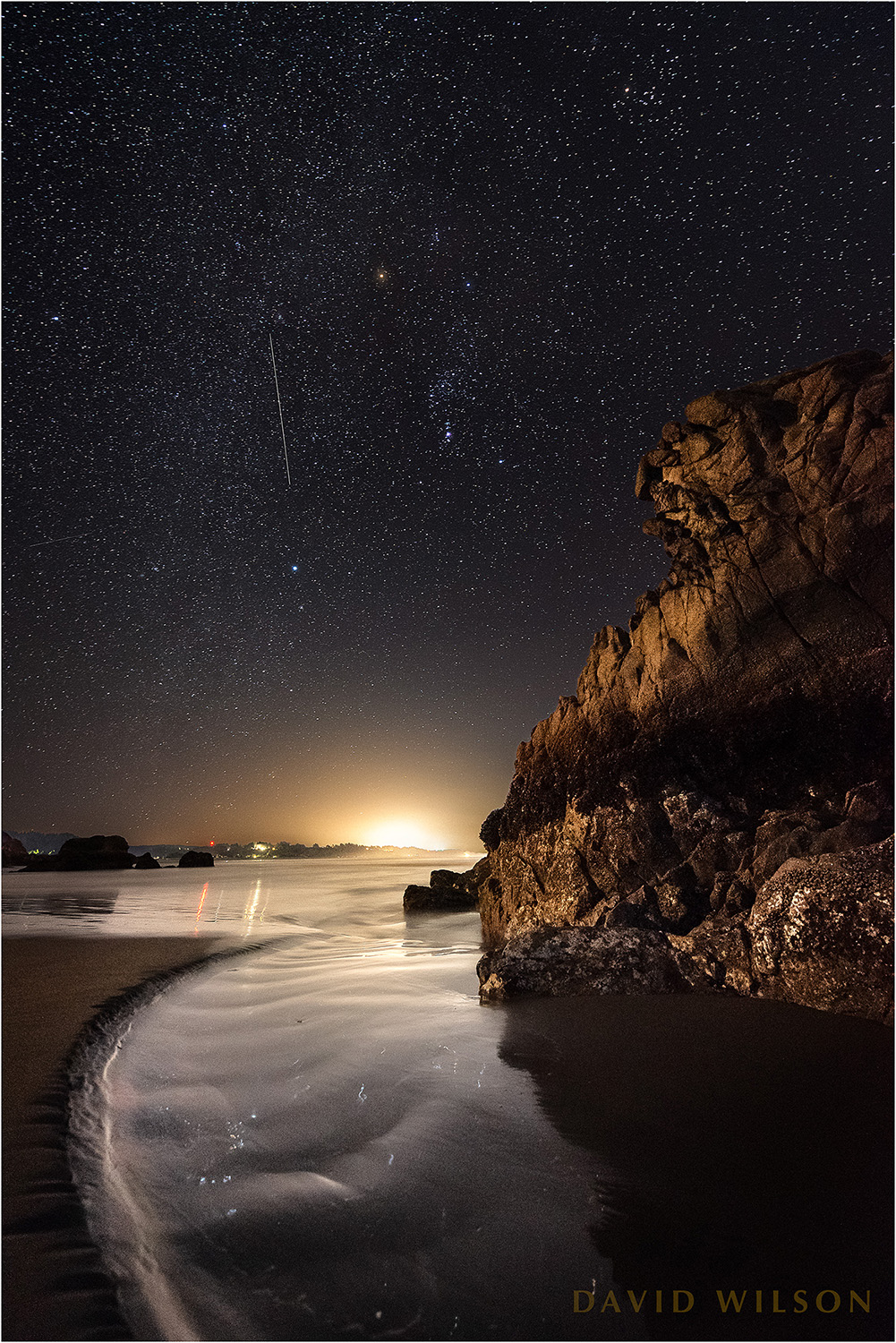 Lights from shore illuminate this great chunk of rock here where the wild coastline intersects with humanity, while above a satellite, an eye in the sky so high, crawled slowly past Orion. Humboldt County, California. February 22, 2019.