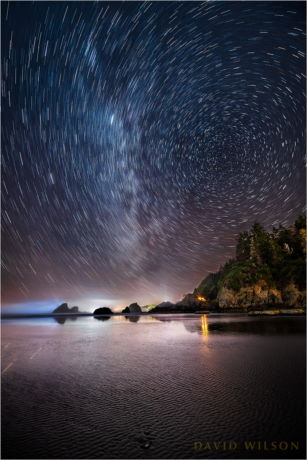 The stars wheel around the north star above the lights from the town of Trinidad. Photographed from Moonstone Beach, Humboldt County, California, this was a single 14-minute exposure.