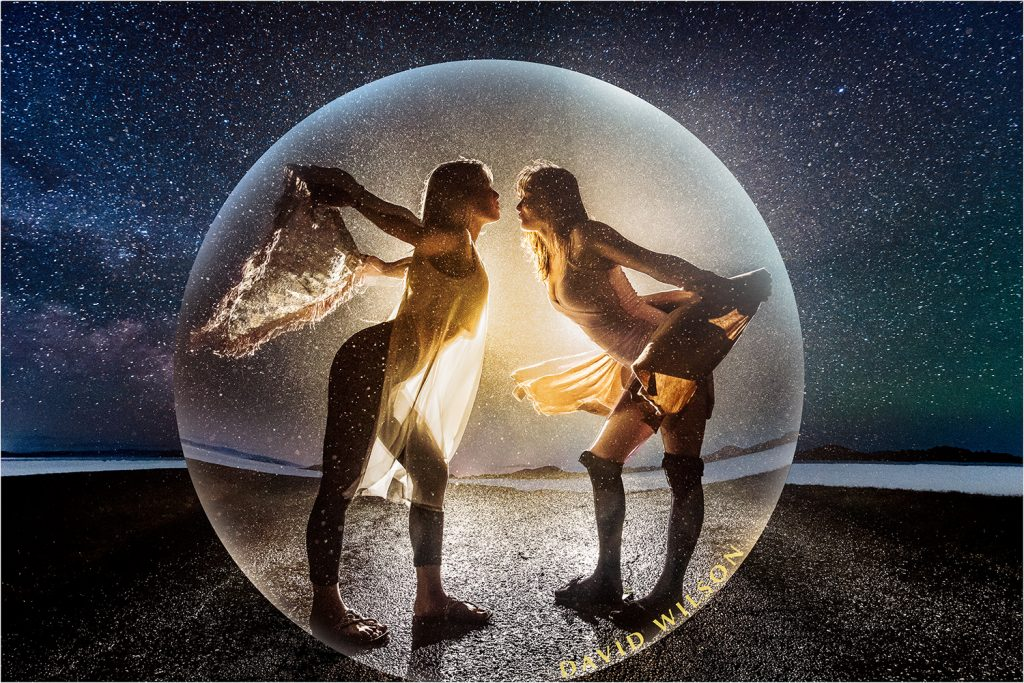 Two goddess women inside a bubble on a dirt road at night with the Milky Way behind them.