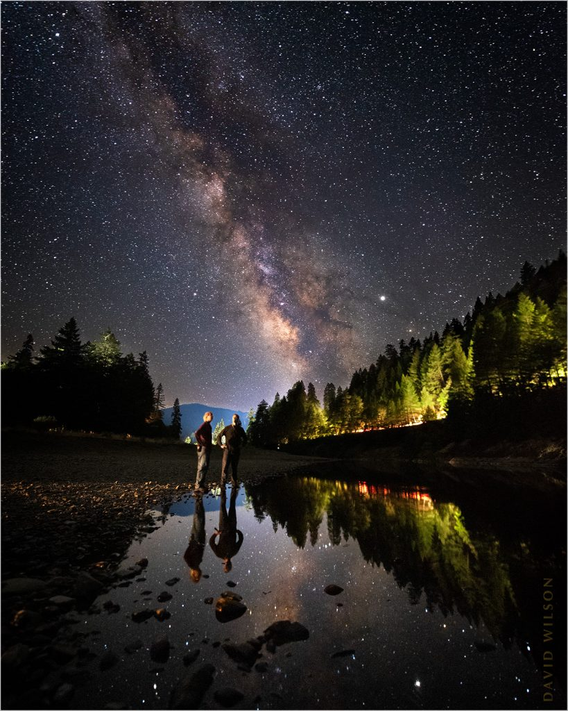 Two guys and their reflections standing on the South Fork Eel River bank beneath the Milky Way