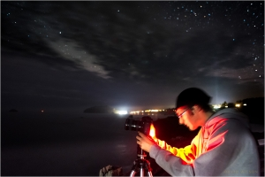 A photographer photographing the over the Pacific nightscape.