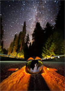 An apparent crystal ball and hole in a road beneath the Milky Way