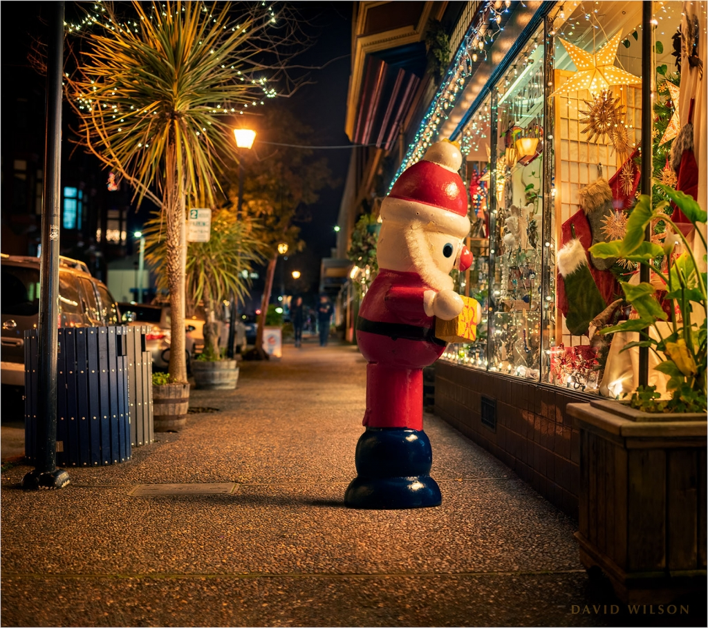 Life-size wooden Santa window shops at christmas