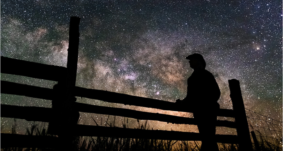Man and fence silhouetted against the night sky and Milky Way
