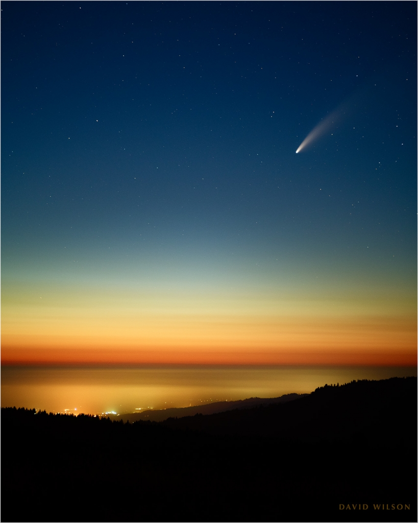 Comet NEOWISE over fading sunset glow, with town lights in the fog