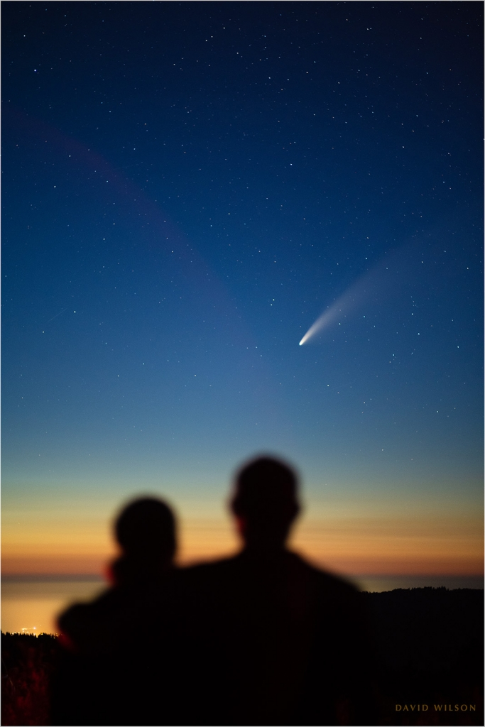 A couple silhouetted against the sky, watching Comet NEOWISE
