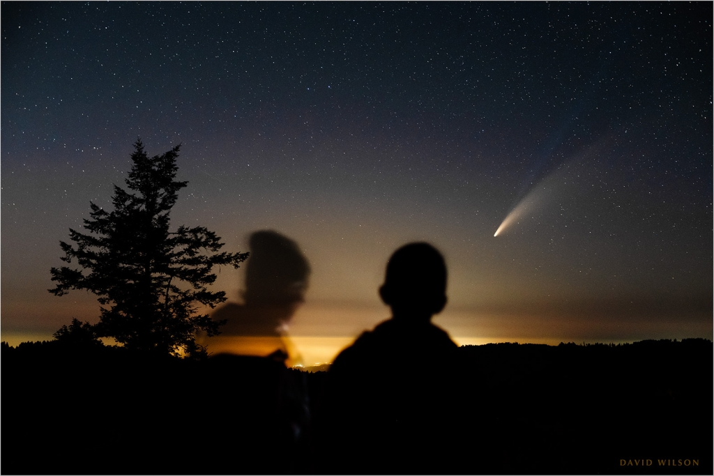 Silhouettes of two stargazers watch Comet NEOWISE .