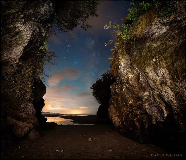 View out of a cave opening onto nighttime beach with Milky Way and stars