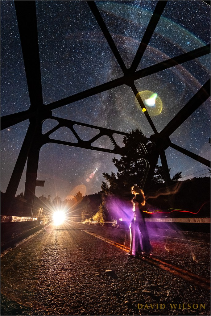 Dancer on a bridge beneath the stars with headlights approaching