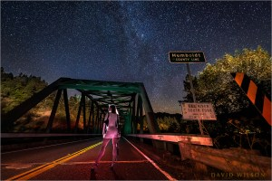 in color: Woman with shotgun on the Cooks Valley Bridge at the Humboldt County Line