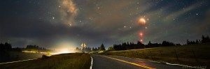 Total lunar eclipse sets over country road, cropped banner shape