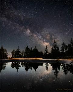 A catchment pond reflects the night sky