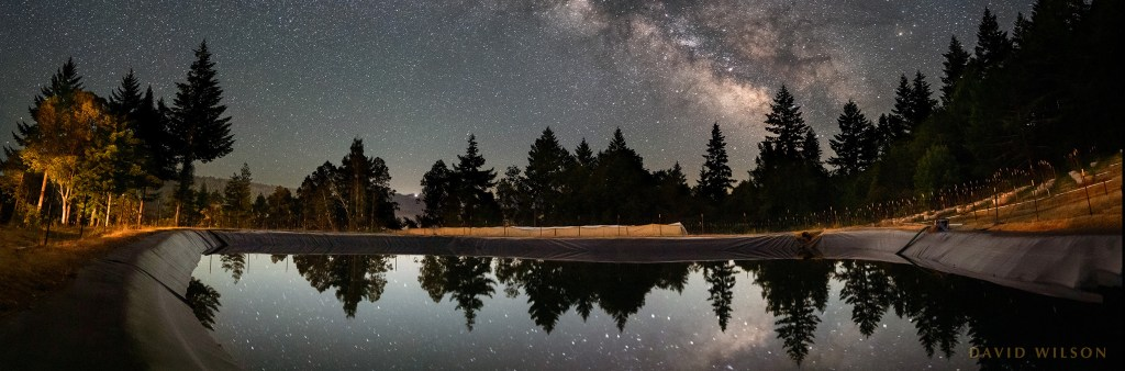 panoramic crop of catchment pond reflecting Milky Way