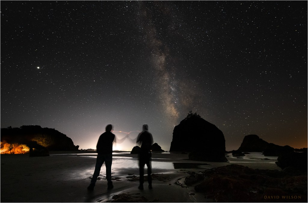 Nighttime beach scene with the silhouettes of two figures.
